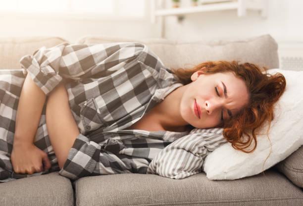 jong meisje dat lijdt aan buikpijn op de bank liggen - buikpijn stockfoto's en -beelden
