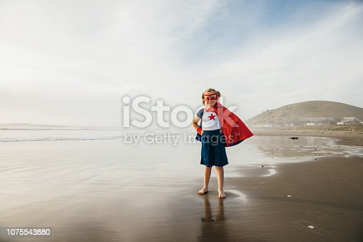 A young girl dressed as a superhero stands barefoot on a California beach with her arm raised to the blue sky. She is ready to save the world. She is confident and has the strength to overcome all adversity. Image taken at Morro Bay, California.
