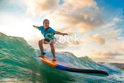 Young girl surfing at sunset.