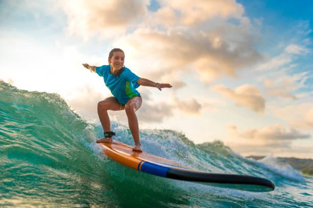 chica joven surf al atardecer - surf fotografías e imágenes de stock