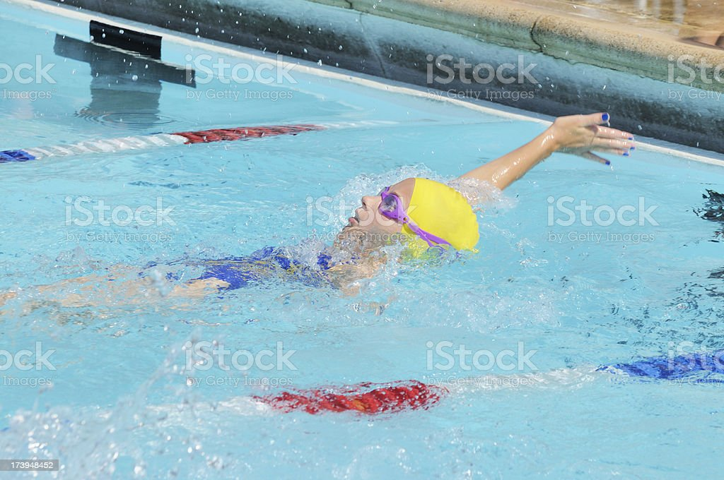Young Girl Swimming and Winning Backstroke Race in Pool stock photo