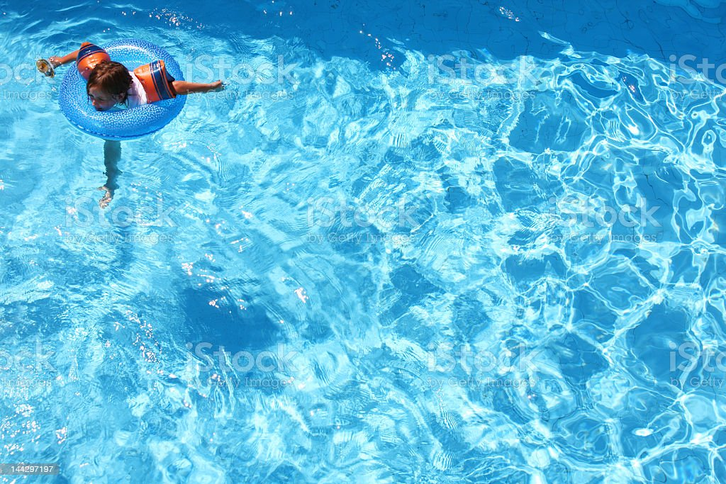 A young girl swimming in clear waters with a blue inner tube stock photo
