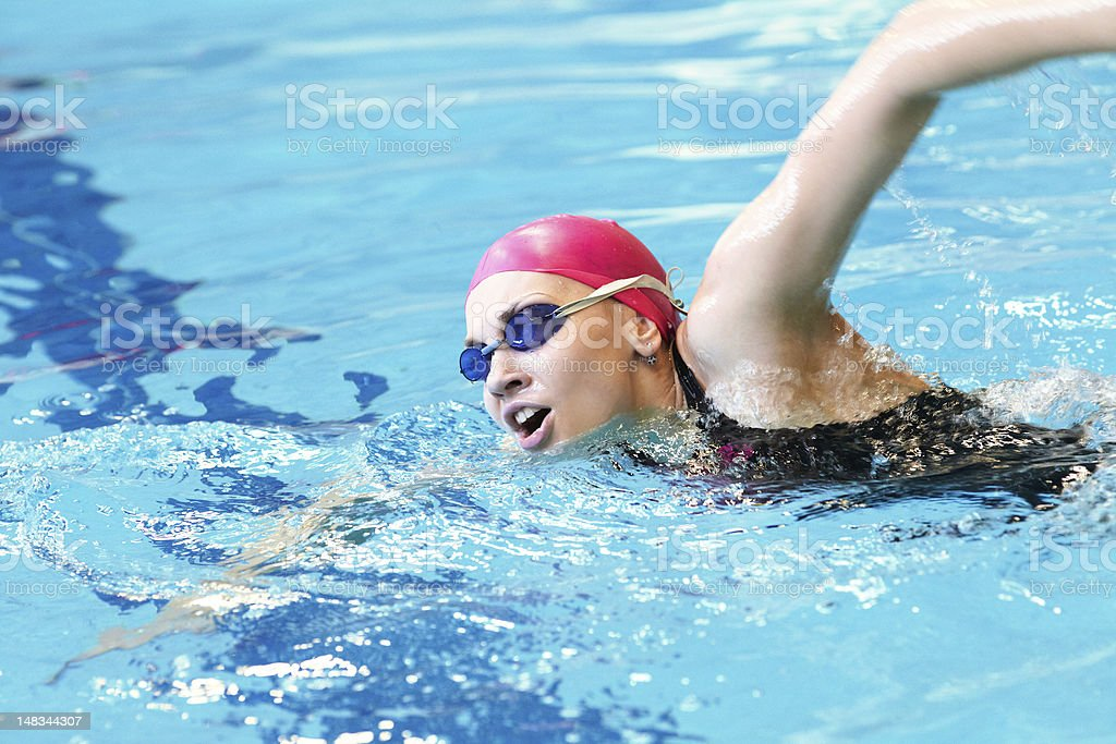young girl swims freestyle stock photo