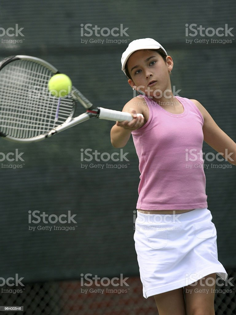 Young girl swinging a tennis racket at a tennis ball - Royalty-free Activity Stock Photo