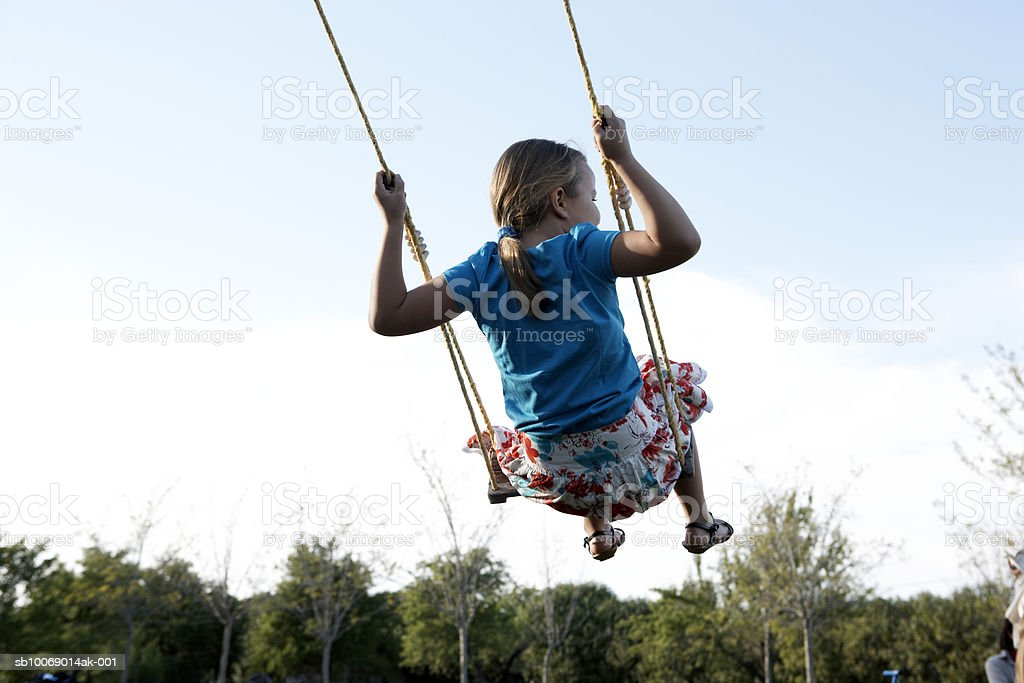 Young girl (8-9) swinging outdoors, rear view royalty-free stock photo