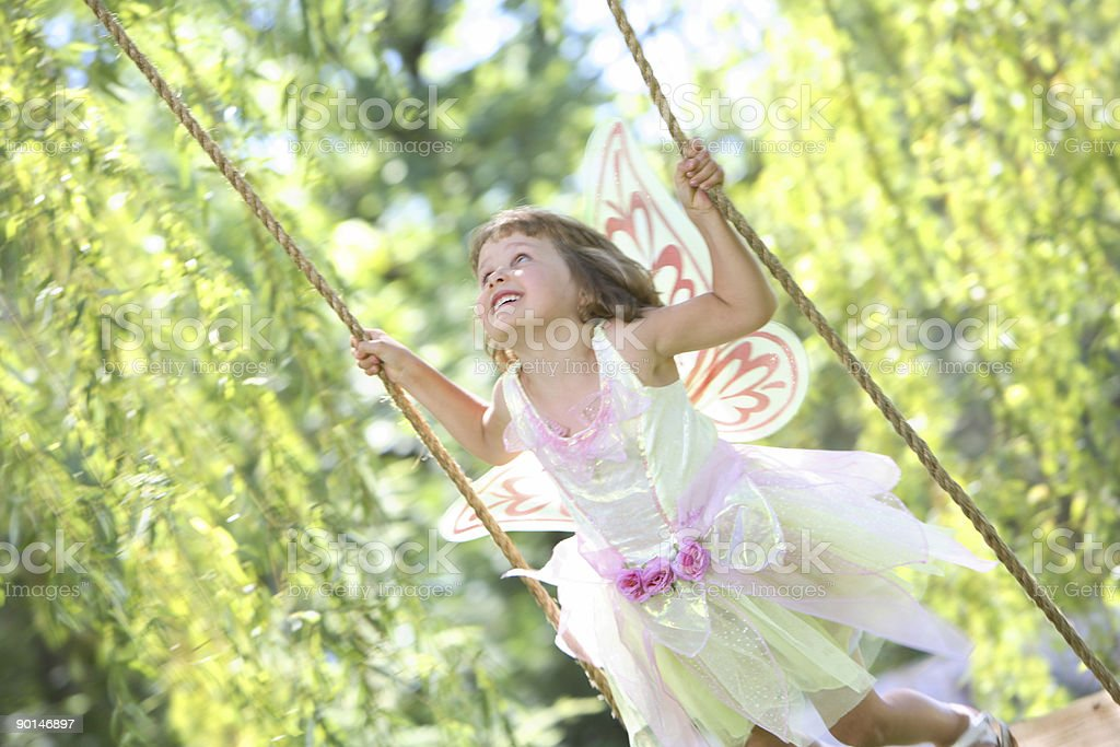 Young girl swinging with a fairy outfit royalty-free stock photo