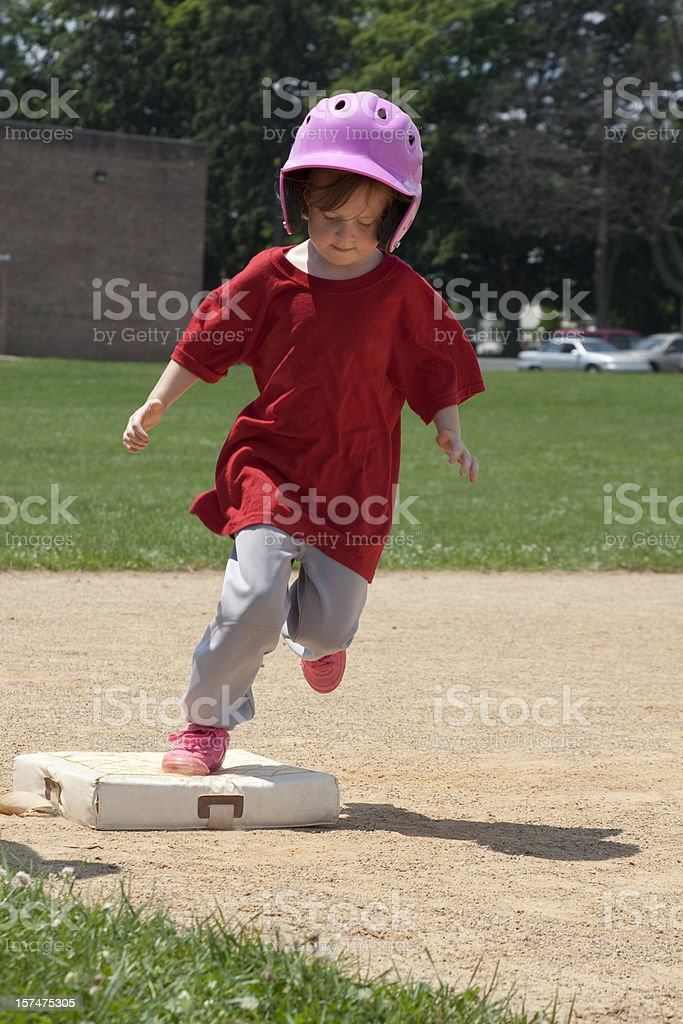 Young Girl Tags Base and Runs for Home stock photo