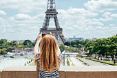 Young girl take photos near the Eiffel tower