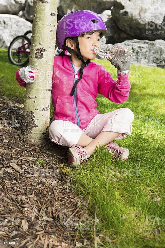 Young girl taking a break while biking in the mountains royalty-free stock photo