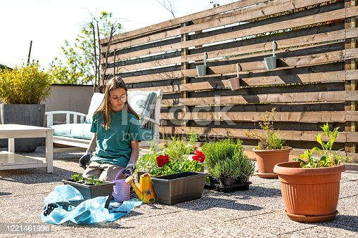 Young caucasian girl taking care of freshly planted seedlings and plants on the terrace.