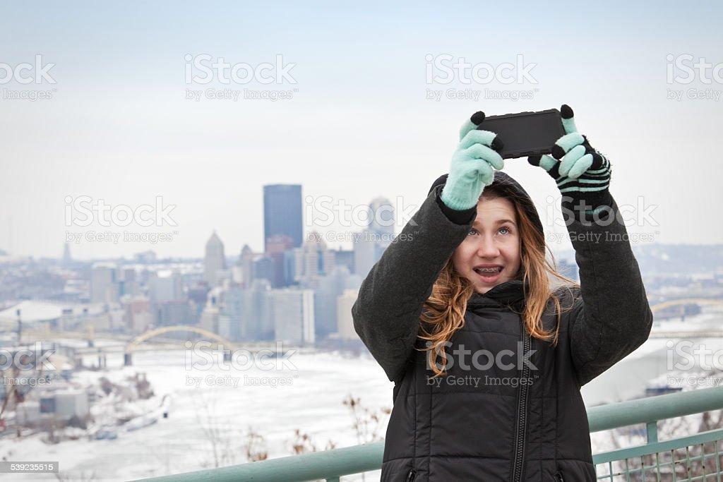 Chica joven tomando autofoto con Horizonte de Pittsburgh foto de stock libre de derechos