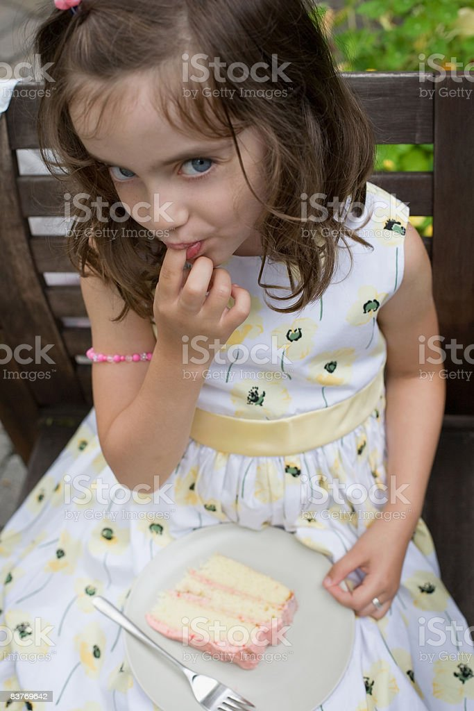 Young girl tasting the icing at birthday party royalty-free stock photo