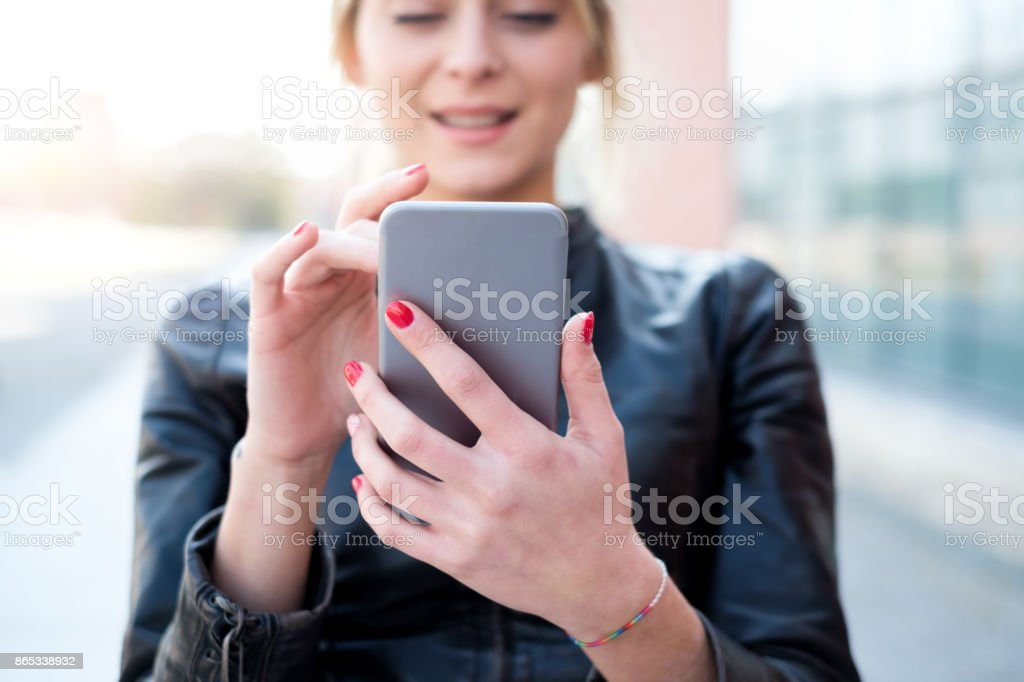 Genç kız manifatura ve şehirde akıllı telefon kullanma stok fotoğrafı