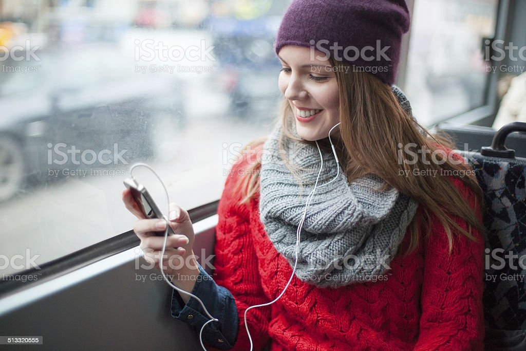 Young girl texting on her phone in public transport stock photo