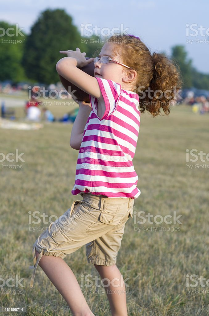 young girl throwing a football royalty-free stock photo