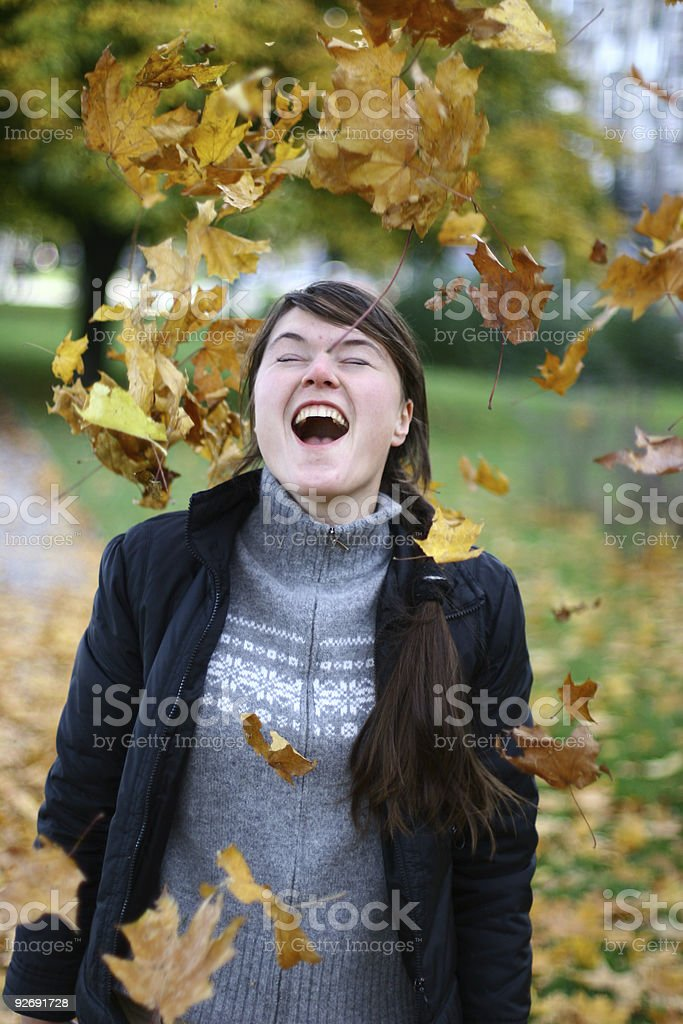 Young girl throwing yellow leaves royalty-free stock photo