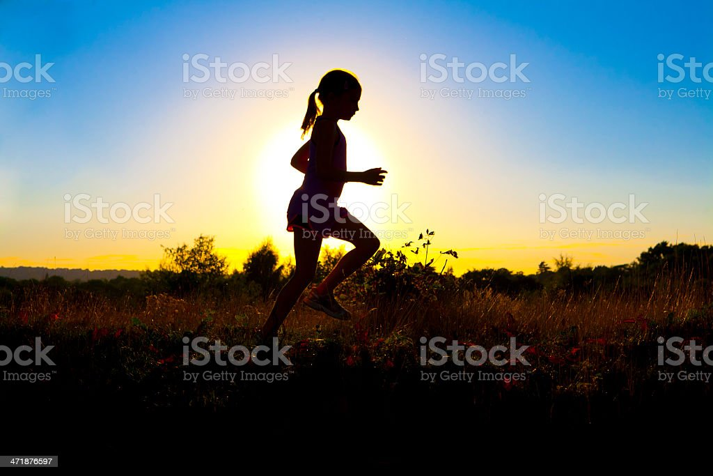 Young girl trail running in the setting sun royalty-free stock photo