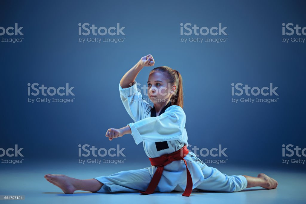 Young girl training karate on blue background stock photo