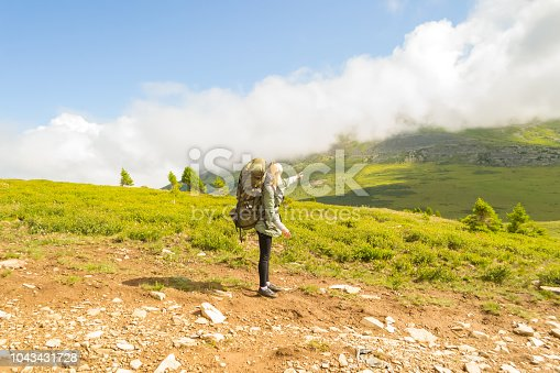 Young girl travel with big green backpack and fishing rod in it indicates the path to go, along the green hill with grass to the adventures under the blue sky and clouds in Altai mountains