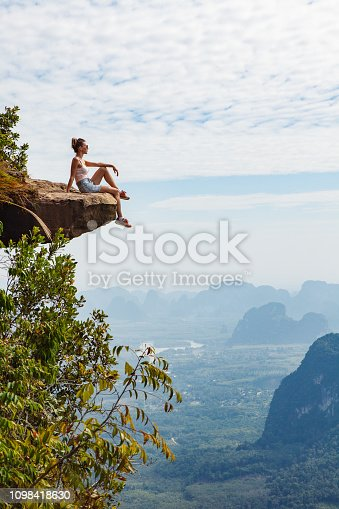 Hipster young girl traveler  sitting on a cliff   relaxing and enjoying a beautiful nature. Travel concept