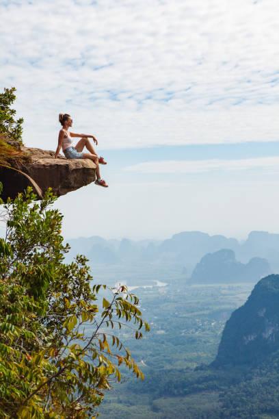 young girl traveler  sitting on a cliff - aventura imagens e fotografias de stock