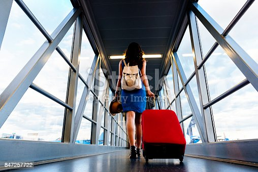 istock Young girl traveler walking with carrying hold suitcase in the airport. 847257722