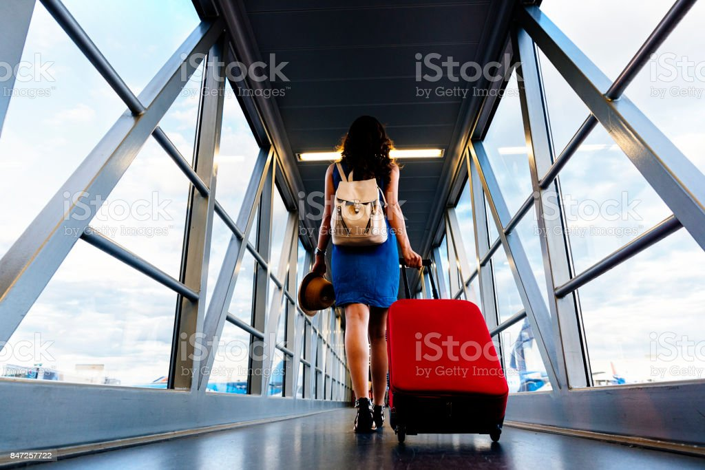 Young girl traveler walking with carrying hold suitcase in the airport. stock photo