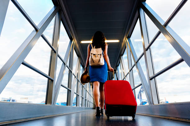 Young girl traveler walking with carrying hold suitcase in the airport. Young girl traveler walking with carrying hold suitcase in the airport. Tourist Concept. passenger stock pictures, royalty-free photos & images