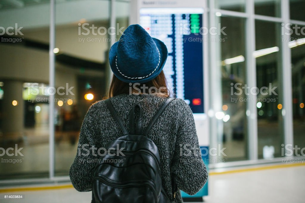 Young girl traveler with a backpack in a hat looks at the information board at the airport. Getting information about the flight. Transfer. stock photo