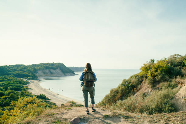 Young girl traveller with backpack standing on a hill and looking at sea view