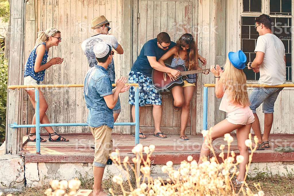 Young girl tries to play guitar with friends photo libre de droits