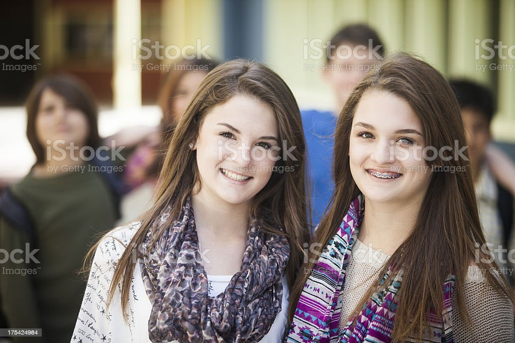 Young Girl Twin Students with Friends in Background stock photo
