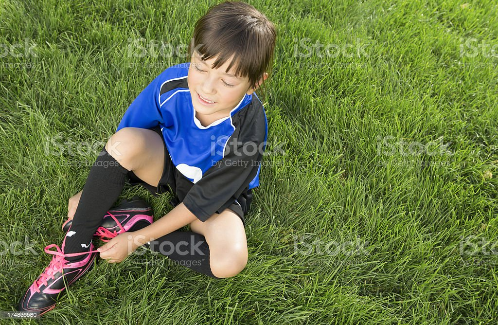 Young girl tying her soccer shoes royalty-free stock photo
