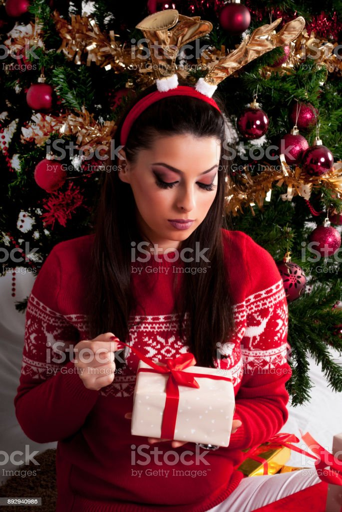 Young girl unlocks gift box and Christmas tree in background stock photo