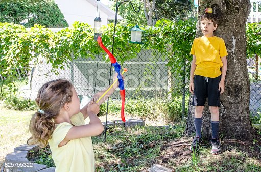 istock Young girl using a bow and arrow and aiming at apple on the head of her brother during a summer day 825755322
