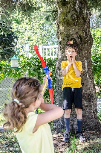 istock Young girl using a bow and arrow and aiming at apple on the head of her brother during a summer day 825755416