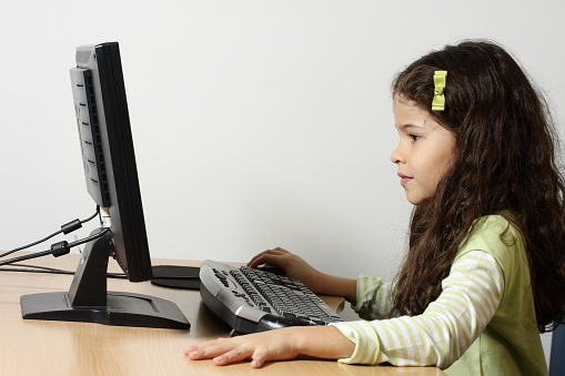 Young Girl Using A Keyboard And Desktop Computer Screen Stock Photo - Download Image Now
