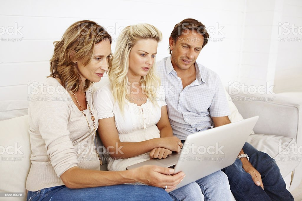 Young girl using laptop with parents at home royalty-free stock photo