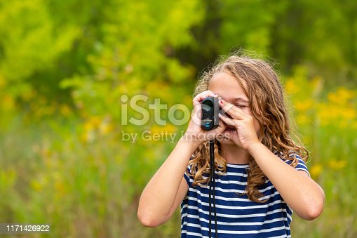 Close-up of a young girl using a rangefinder. She is at an outdoor archery range, but all that is visible in this image behind her are trees and wild grasses. The girl is wearing a blue and white striped t-shirt on this beautiful early autumn day.