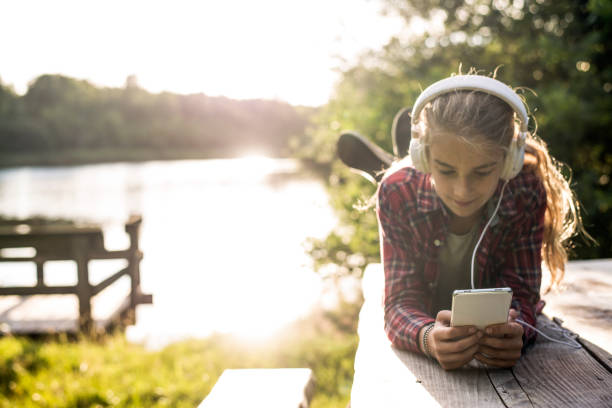 Young girl using smartphone at the lake stock photo