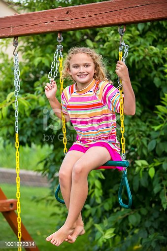Close-up of a young girl using the trapeze bar on her outdoor playset as a swing. She is sitting on the bar and smiling at the camera. The girl is wearing a pink striped rash guard swim shirt and pink swim skirt, as she has also been playing in the back yard pool on this summer evening.