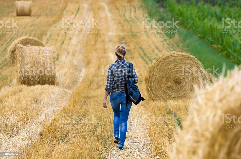 Young girl walking across lawn field with round hay bale stock photo