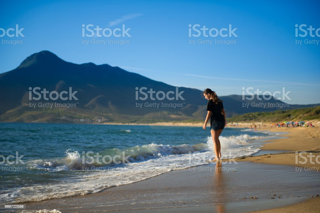 Young girl walking along the shore stock photo