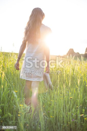istock Young girl walking in high grass field 950836672