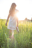 Young beautiful blond girl walking in a romantic background setting outdoors in field with high grass. Bright sunlit background.