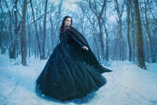 junge mädchen zu fuß im winterwald - gothic kleid stock-fotos und bilder