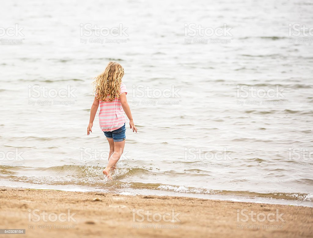 Young Girl Walking Into Water At Beach stock photo