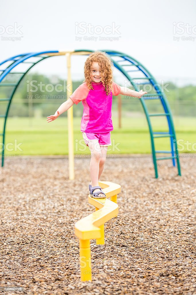 Young Girl Walking on Balance Beam at Playground stock photo