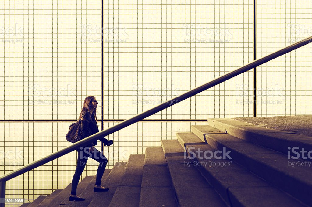 Young girl walking stairs in a city enviroment stock photo
