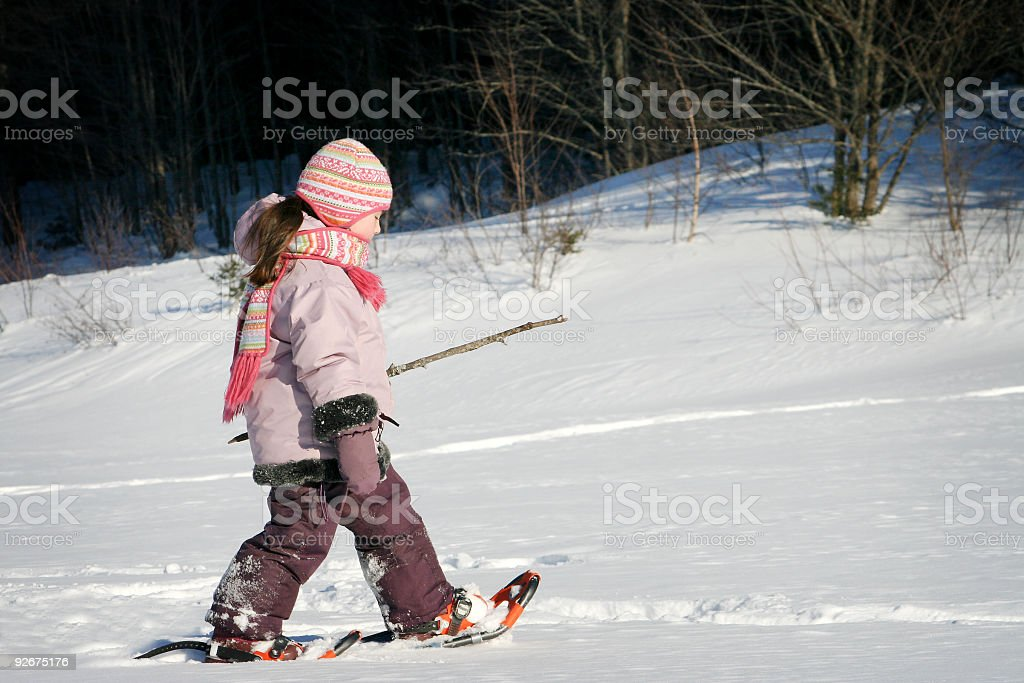 Young girl walking with snowshoes royalty-free stock photo